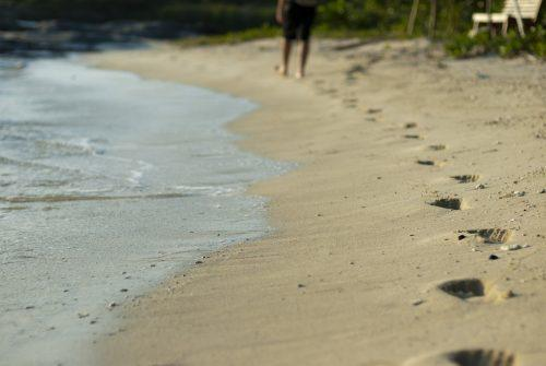 Man disappearing into the distance walking on a sandy beach close to the sea with footprints